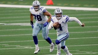 Dallas Cowboys quarterback Dak Prescott scrambles with the ball in hand