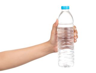 a woman's hand holds up a water bottle
