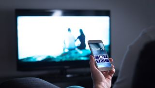 A man's hand holds a smartphone while a flatscreen TV is on in the background.