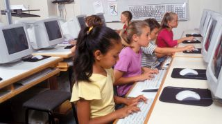kids work at computers in a classroom