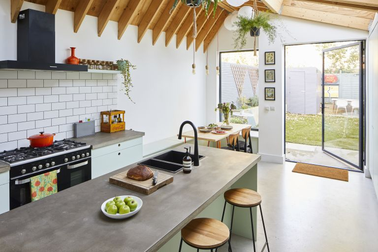 A kitchen with large pivot door and picture window, concrete-effect worktops and floor, and exposed beams in the pitched extension roof