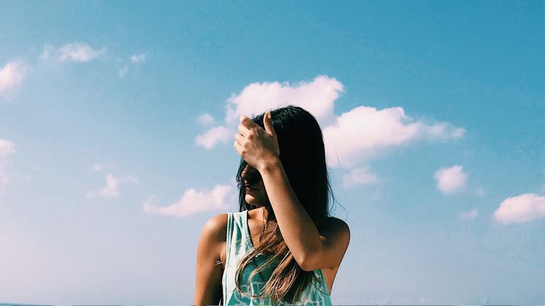 A woman is seen With Hand In Hair Standing Against Sky