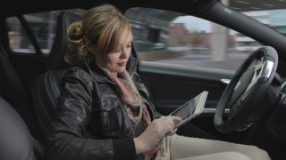 Woman travelling in driverless car using iPad