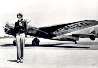 Amelia Earhart, who has a tall, thin body, stands in front of the Lockheed Electra in which she disappeared in July 1937.