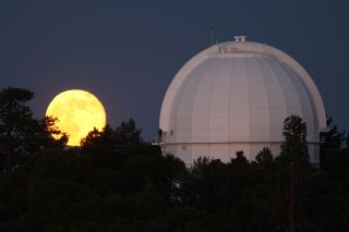 A supermoon rises behind the Mount Wilson Observatory on July 12, 2014, northeast of Los Angeles, California.