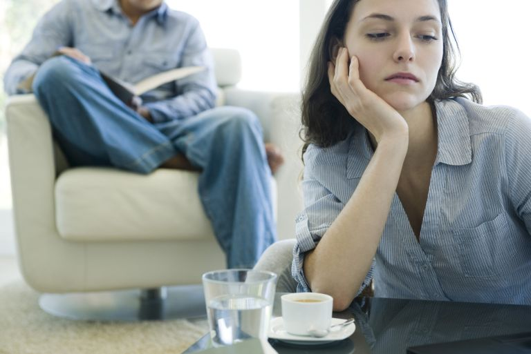 Woman leaning on elbow looking sad, man reading on sofa in background - what is a situationship
