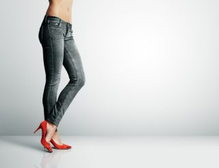 A woman stands wearing skinny jeans.