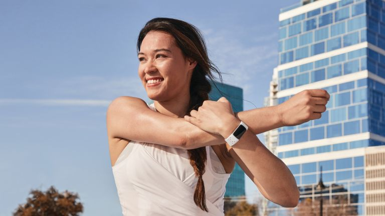 Person stretching outside wearing the Fitbit Charge 5 fitness tracker