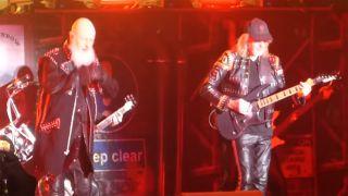 Glenn Tipton (right) performing live alongside Judas Priest
