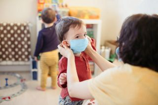 An adult puts a mask on a toddler.