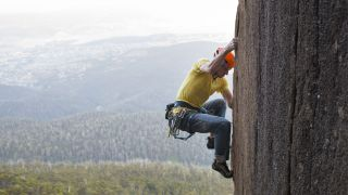 a guide to climbing rating systems: climber on rock wall