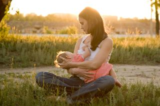 A woman breast-feeds her baby outdoors.