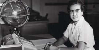 Young Katherine Johnson sits at her desk with a big globe