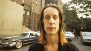 Todd Rundgren standing by an apartment block in New York July 1974