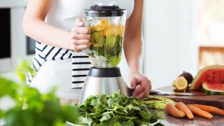 Blender full of fruit and vegetables on a kitchen countertop surrounded by more fruit and veg