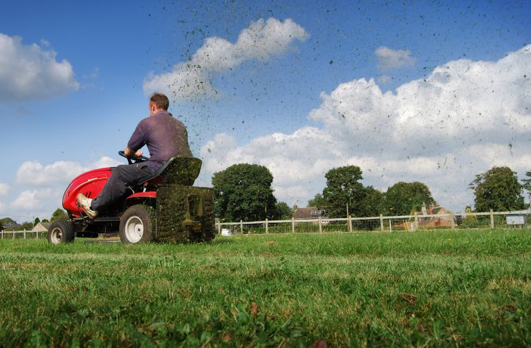 man on the best riding lawn mower featured on grass