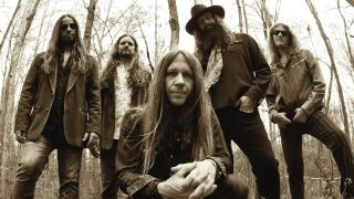 Blackberry Smoke standing in the woods, frontman Charlie Starr kneeling at the front of the group and looking at the camera.