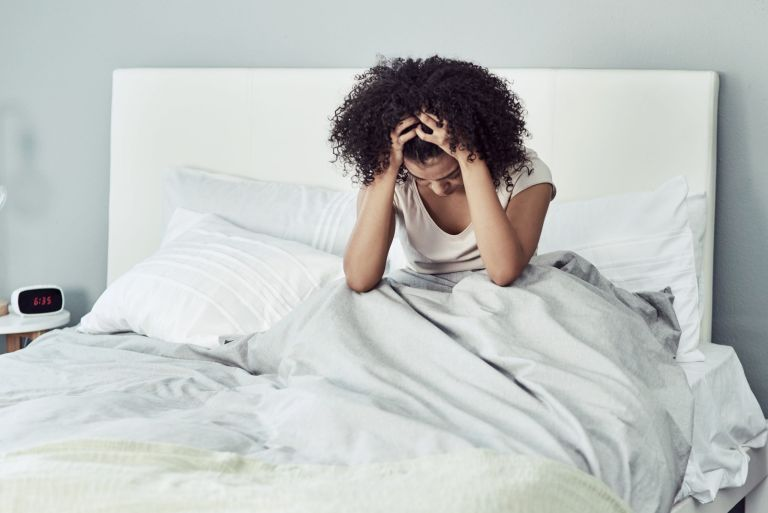 Sexual anxiety: woman in bedroom looking stressed