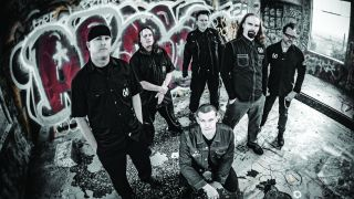 A press shot of Mudface taken in 2016, stood in front of a graffiti wall