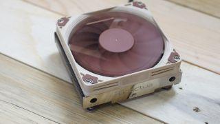 A brown and beige Heatsink Fan NoctuaNH-L9i CPU cooler on wooden slats.