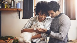 Shot of a couple with their cat at home