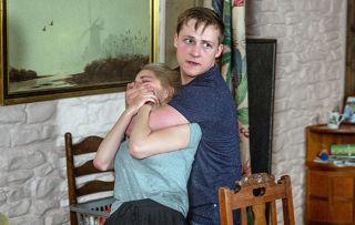 Lachlan White has his hand over the mouth of Belle Dingle in Emmerdale