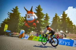 In game screenshot of a CCC rider climbing in Zwift past a recreation of Didi the devil