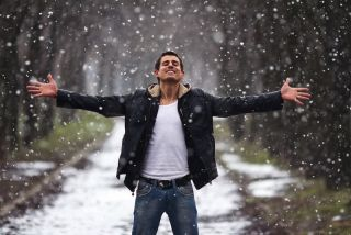 A man looks happy on a snowy day.