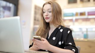 Best website hosting services: young woman using phone and laptop