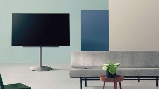 Loewe TV on stand, next to sofa