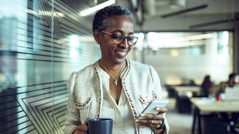 Close up of a senior businesswoman using a phone while having coffee in the office