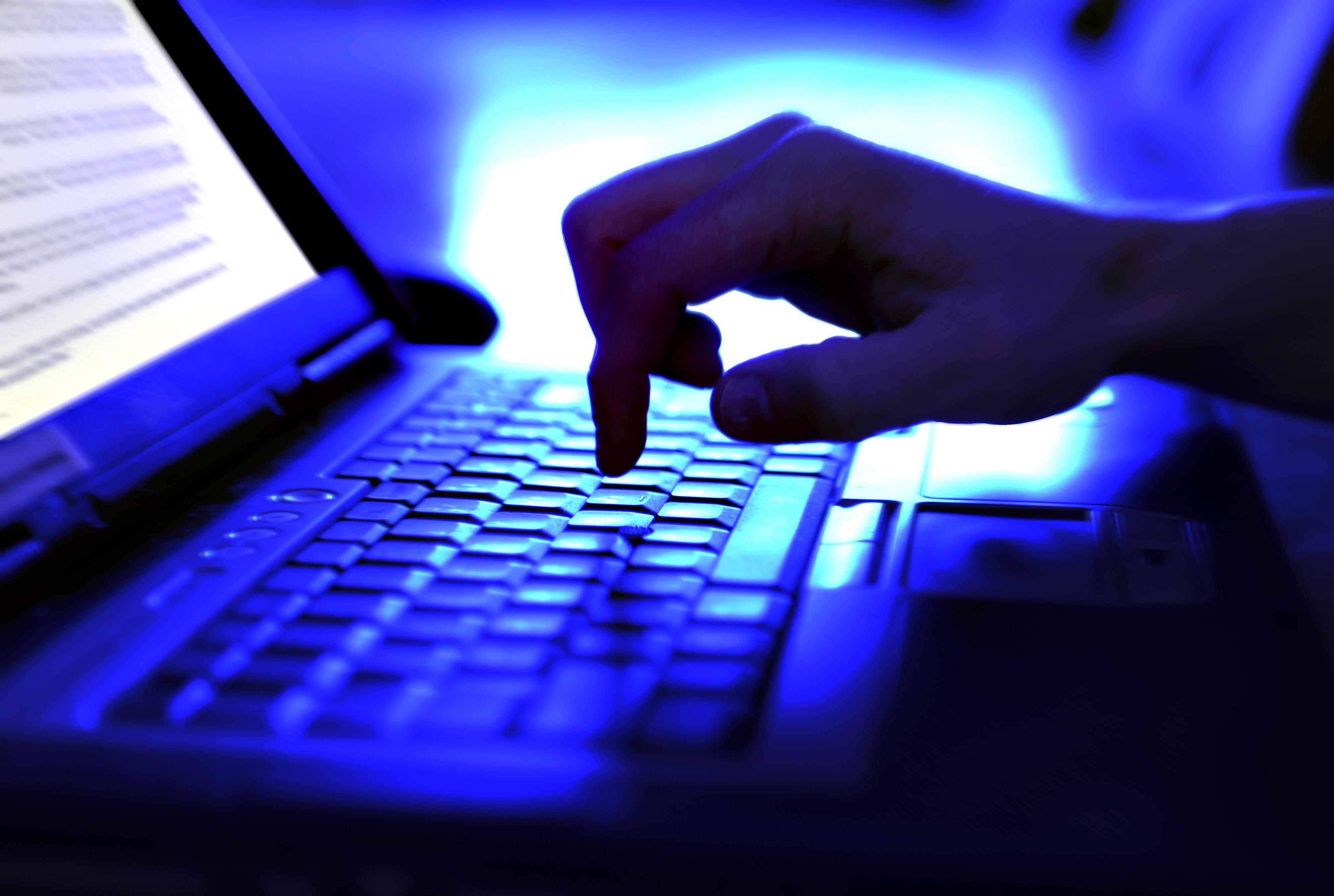 website seo - person typing on keyboard in blue-lit room