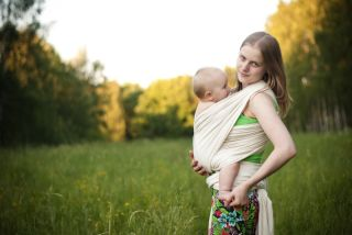 An attachment mother wearing her baby in a sling.