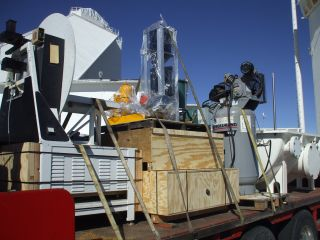 Components are placed on a flatbed trailer for the trip off Kitt Peak. All critical optics and electronics were shrink-wrapped and went down in a covered semi. Everything will be transferred to an enclosed trailer for the cross-country trip. In the backgr