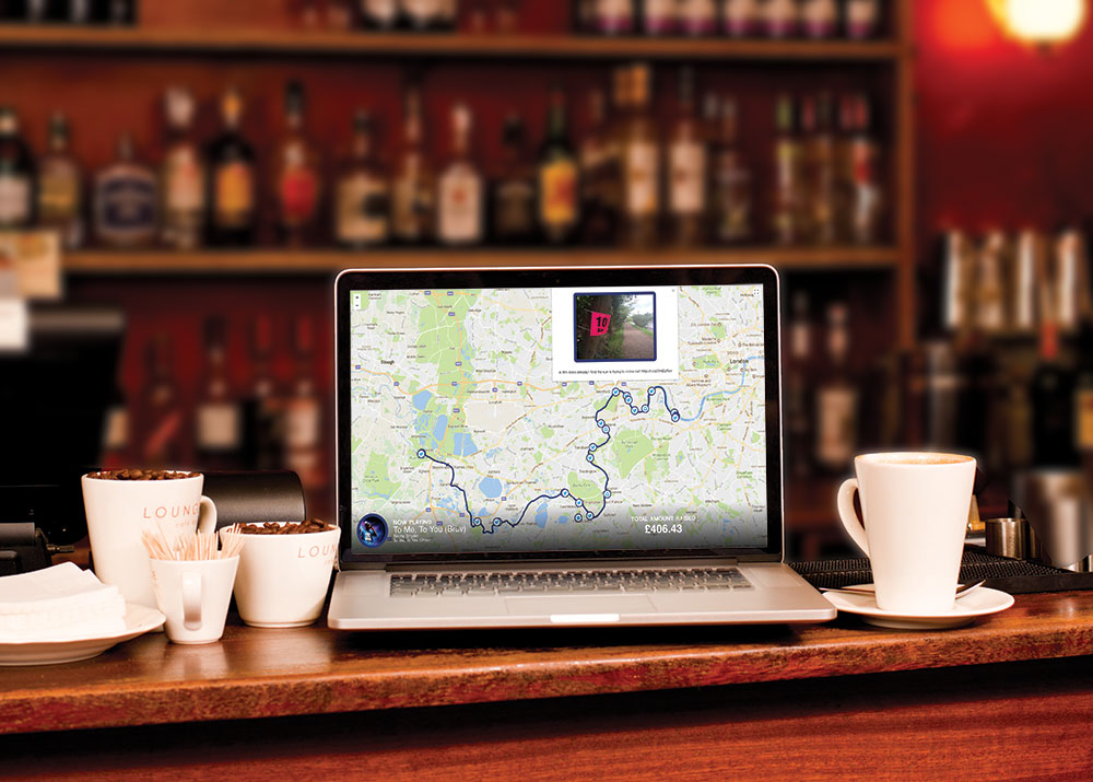 Laptop in a cafe displaying a map route