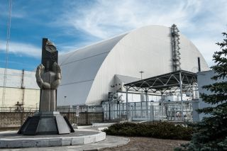 New Safe Confinement structure covers the original sarcophagus and radiation underneath it.