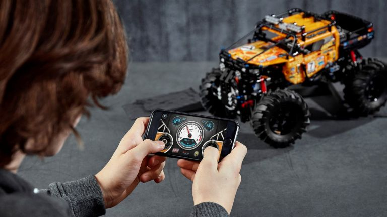 Boy playing with a remote control car from a Lego Technic set