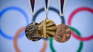 Gold, silver and bronze medals in front of the Olympics rings logo