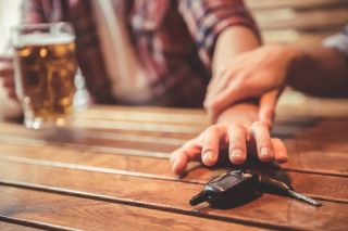 A stock photo of a man drinking while reaching for car keys while his friend stops him.