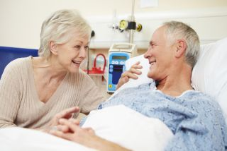 An older couple talks while the man lays in a hospital bed