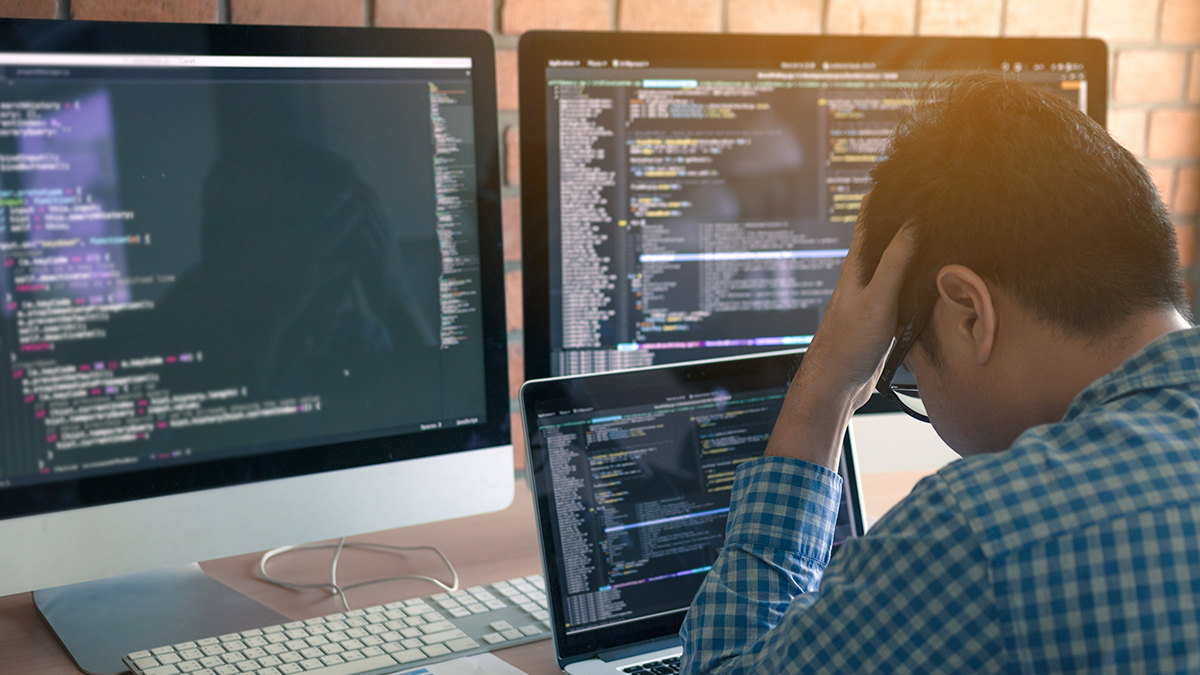 Overworked tech professional sitting in front of multiple monitors