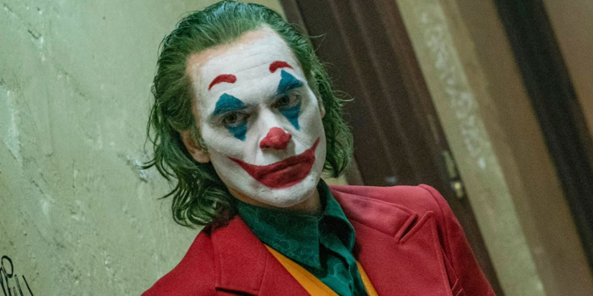 Joker Arthur in full makeup walking down a hall