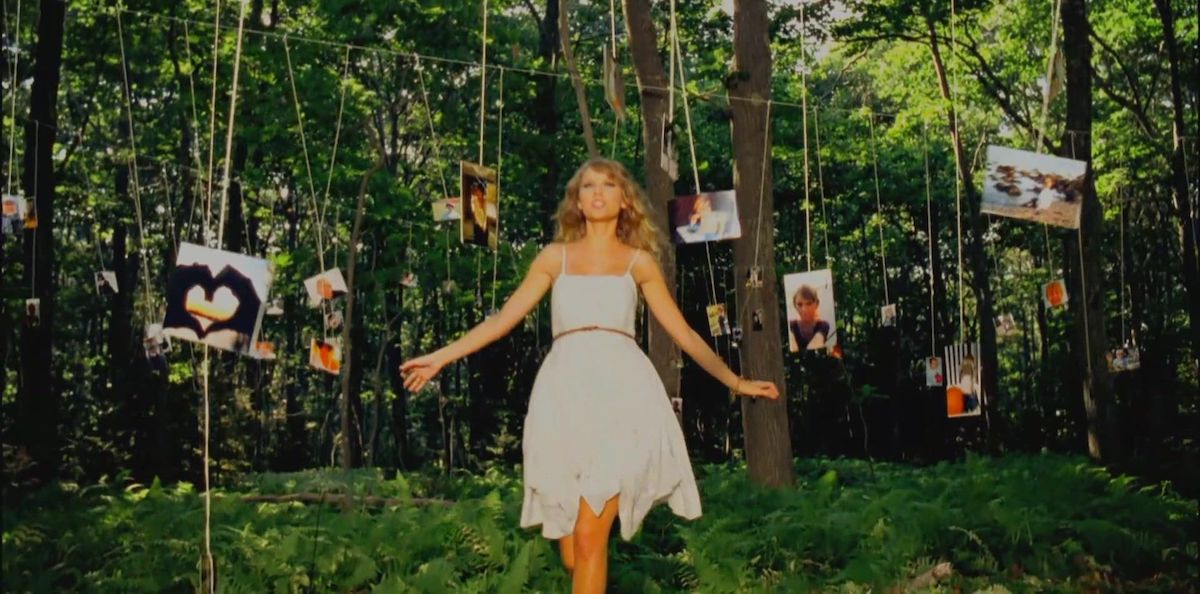 Taylor Swift in a forest full of pictures in the Mine music video