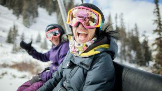 Two women laugh on a ski lift