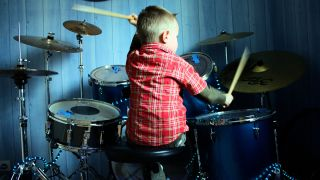 Child in a red stripy shirt plays a blue drum kit