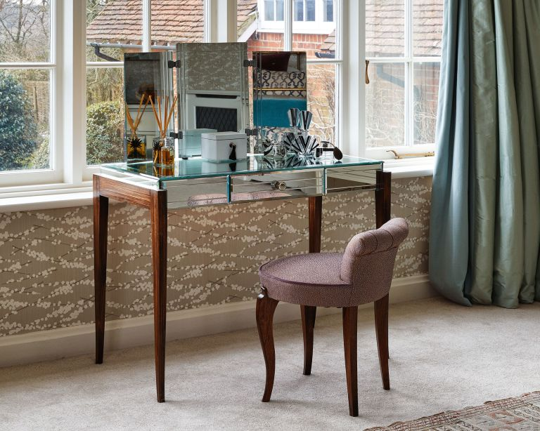 An example of dressing table ideas showing a mirrored dressing table in front of a window with an upholstered chair