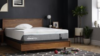 Tempur-Pedic deals and promo codes: photograph showing a mattress on a wooden frame in a bedroom