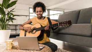 Woman plays acoustic guitar sat on a sofa in front of a laptop