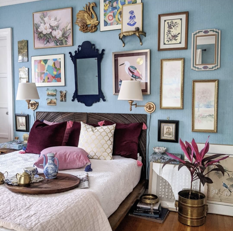 blue bedroom with eclectic gallery wall behind headboard