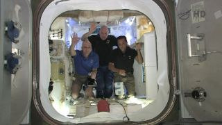 NASA astronauts Don Pettit (right) and Joe Acaba (left) with European Space Agency (ESA) astronaut Andre Kuipers wave from inside SpaceX's Dragon spacecraft, now attached to the International Space Station